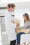 给患者一头被充塞的熊的医生 免版税库存照片