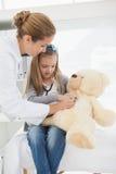 给患者一头被充塞的熊的医生 库存照片