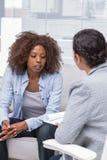 患者坐沙发和谈话与治疗师 免版税库存照片