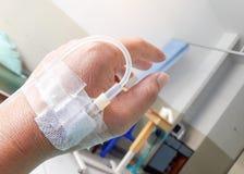 患者的手在接受在床上的滴水一个食盐水我 免版税库存图片