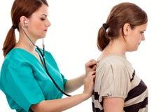 年轻患者的医生审查的肺有听诊器的 免版税库存图片