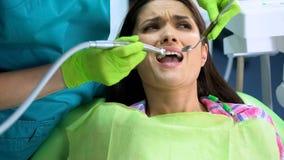 患者被惊吓牙科钻子,有密集的牙痛,口腔医学 库存照片