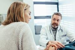 患者谈话与医生在诊所的咨询时 库存图片