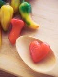 悦人的仿制果子在心脏在woodedn桌上塑造 库存图片