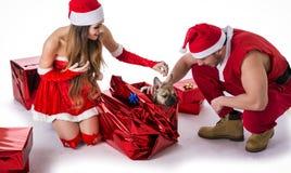 悦目夫妇在有圣诞节礼物的圣诞老人帽子 免版税库存照片