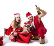 悦目夫妇在有圣诞节礼物的圣诞老人帽子 图库摄影