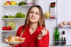悦目年轻女性画象皱眉面孔当气味鲜美sandwhiches,在有食物近的被打开的冰箱的厨房里充分站立 免版税库存照片