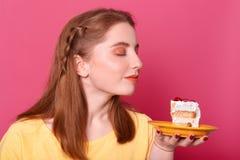 悦目年轻女性,模型水平的射击嗅鲜美点心,concentared在巨大的蛋糕,要吃 免版税库存照片