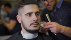 您喜爱的理发店的年轻,勇敢的行家 参与他的胡子大师,用途整理者塑造根据 股票视频