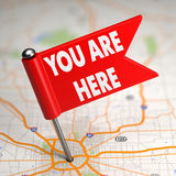 您在这里-在地图背景的小旗子 免版税库存照片