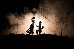 您是否与我结婚?停留在膝盖和提出提议对于他可爱的女孩的年轻人剪影反对黑暗的被定调子的backgrou 免版税图库摄影
