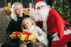 您的妈妈和爸爸爱您 父亲穿戴的圣诞老人服装 免版税库存照片