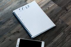 您的想法的笔记 关于木背景的笔记2018年与一个手机 库存照片