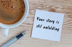 您的故事仍然展开刺激题字在笔记薄靠近早晨咖啡,与空的空间的顶视图 库存照片
