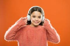 您的移动设备的最佳的自由音乐应用程序 享受声音 女孩逗人喜爱的小孩佩带耳机听音乐 ?? 库存照片