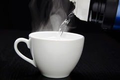 您的茶杯的倾吐的水 库存图片