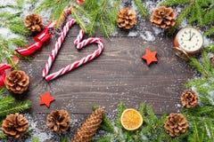 您的项目的圣诞节或新年框架与拷贝空间 在雪的圣诞节冷杉木与锥体,棒棒糖,葡萄酒时钟, 免版税库存图片