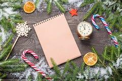 您的项目的圣诞节或新年框架与拷贝空间 在雪的圣诞节冷杉木与锥体,棒棒糖,葡萄酒时钟, 库存图片