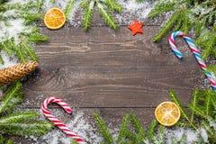 您的项目的圣诞节或新年框架与拷贝空间 在雪的圣诞节冷杉木与锥体,棒棒糖,装饰星 库存照片