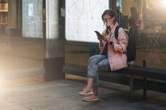 您背景设计花卉晚上无缝的夏天 使用智能手机,镜片的少妇有背包的坐在公共汽车站, 行家女孩聊天 免版税库存照片