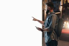 您背景设计花卉晚上无缝的夏天 年轻有胡子的人在城市街道上站立并且接触大发光的触摸屏幕,拿着智能手机 免版税图库摄影