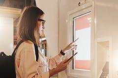 您背景设计花卉晚上无缝的夏天 镜片的少妇有背包的在城市街道上站立,接触数字显示,拿着智能手机 免版税库存照片