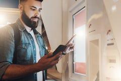 您背景设计花卉晚上无缝的夏天 年轻有胡子的人在城市街道上站立并且接触数字显示,当在智能手机时屏幕上的神色  免版税库存照片