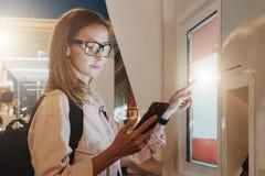 您背景设计花卉晚上无缝的夏天 镜片的少妇有背包的在城市街道上站立,接触数字显示,拿着智能手机 免版税库存图片