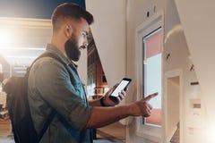 您背景设计花卉晚上无缝的夏天 年轻有胡子的人在城市街道上站立并且接触数字显示,当在智能手机时屏幕上的神色  库存照片
