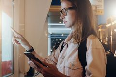您背景设计花卉晚上无缝的夏天 镜片的少妇有背包的在城市街道上站立,接触数字显示,拿着智能手机 库存照片