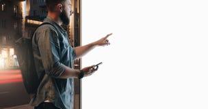 您背景设计花卉晚上无缝的夏天 年轻有胡子的人在城市街道上站立并且接触大发光的触摸屏幕,拿着智能手机 库存照片