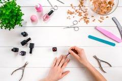 绘您自己的钉子 修指甲器和指甲油在木背景 免版税库存图片