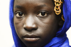 悲伤和绝望标志-有一条蓝色围巾的逗人喜爱的非洲学校女孩在她的头 免版税库存照片