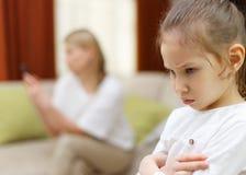 悲伤女孩 乏味女儿画象有使用在床上的母亲的手机 免版税图库摄影