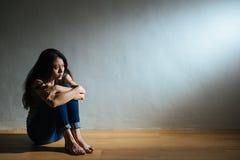 悲伤少妇坐木地板 免版税库存图片