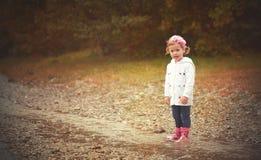 悲伤逗人喜爱的女婴在使用在自然的雨中 免版税库存照片