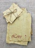 情书和信封由与红色花的古色古香的parchmnet纸制成 图库摄影