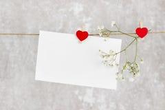 情书在绳索和一朵花垂悬在轻的背景 免版税库存照片