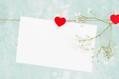 情书在绳索和一朵花垂悬在蓝色背景 免版税库存图片