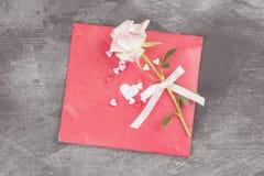 情书在绳索和一朵花垂悬在黑暗的背景 免版税库存图片