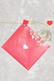 情书在绳索和一朵花垂悬在轻的背景 免版税库存图片