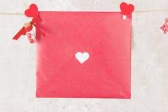 情书在绳索和一朵花垂悬在轻的背景 库存图片