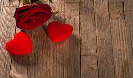 情人节、红色天鹅绒心脏在木地板上和玫瑰 免版税库存图片