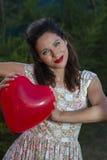 情人节。有一件礼物的美丽的微笑的妇女以形式 免版税库存图片