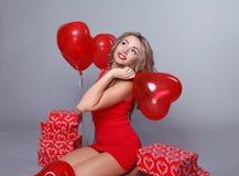 情人节。 有红色重点气球的美丽的愉快的妇女 免版税库存图片