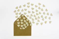 情人节与心脏的贺卡信封 金黄心脏倾吐在白色隔绝的信封外面 飞行重点 免版税图库摄影