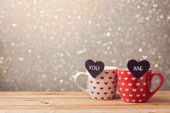 情人节与杯子和心脏夫妇的假日庆祝在bokeh 免版税库存照片