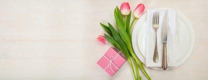 情人节与桃红色郁金香和一件礼物的桌设置在白色木背景 顶视图,拷贝空间,横幅 免版税库存图片