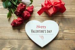 情人节与花束红色玫瑰的贺卡开花,心脏作为空白和在木桌上的礼物盒 免版税库存照片