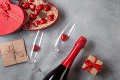情人节与香槟玻璃和糖果心脏的贺卡在石背景 与空间的顶视图您的问候的 库存照片